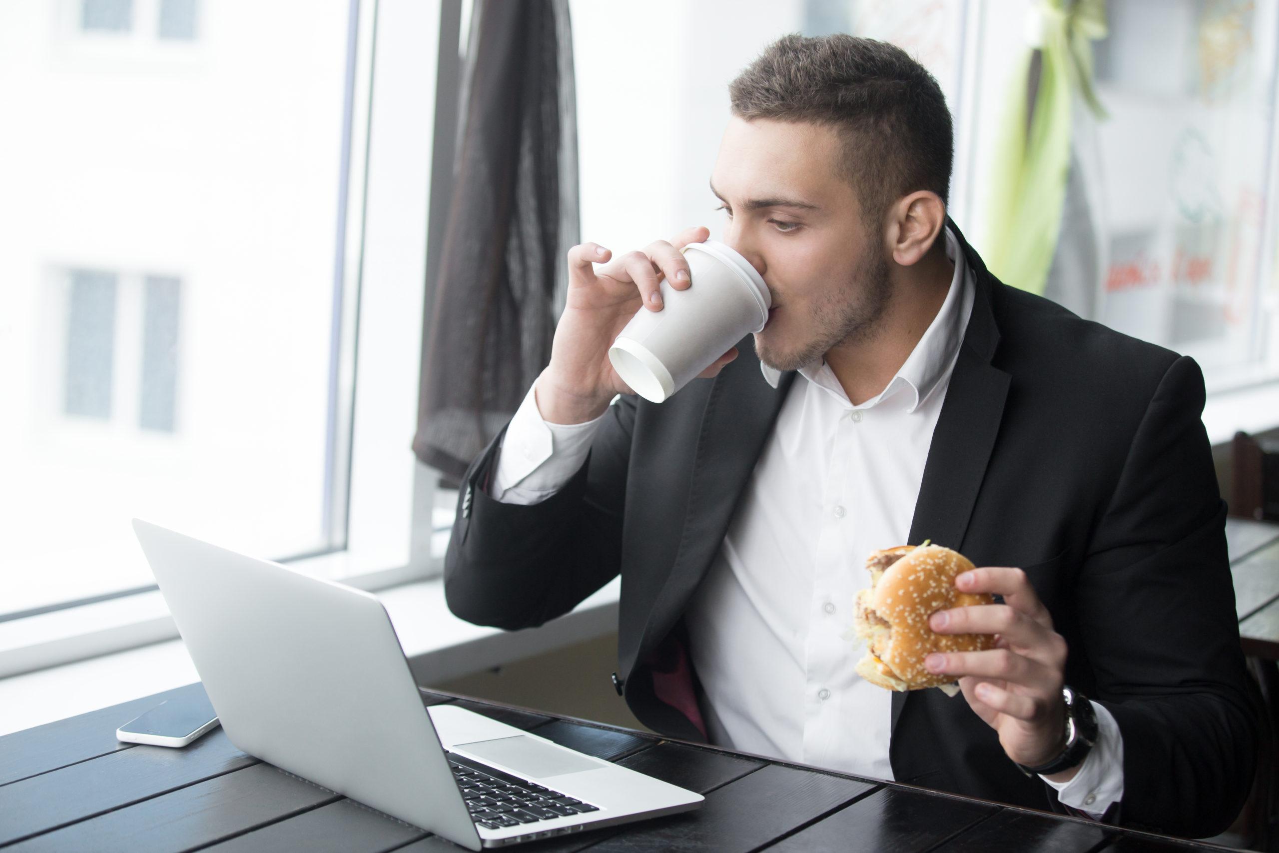 Hombre sedentario comiendo trabajando